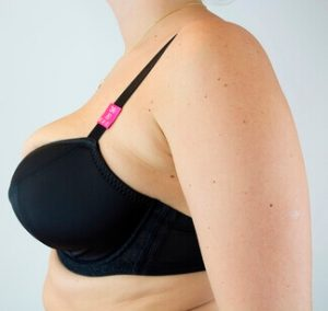 A woman in a bra with cups that are smaller than her breasts. Shows the need to know what's my bra size